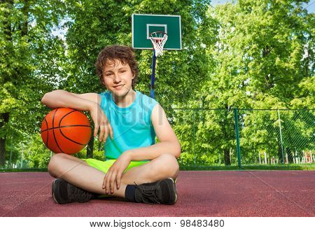 Boy sitting alone with elbow on the ball