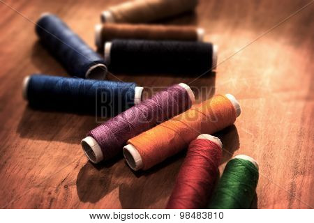 Colored sewing threads on a old work table with impressional tone and feel. Shallow depth of field.