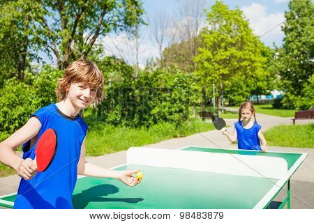 Boy with racket serves table tennis ball to girl