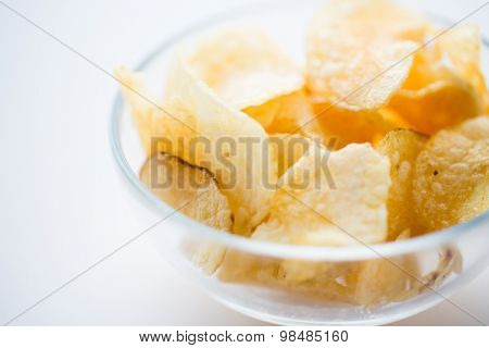 fast food, junk-food, cuisine and eating concept - close up of crunchy potato crisps in glass bowl