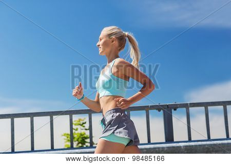 fitness, sport, people and healthy lifestyle concept - smiling young woman with heart rate watch running outdoors