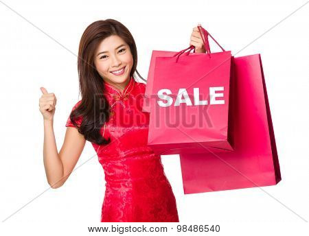 Chinese woman hold with shopping bag and thumb up for showing a word sale
