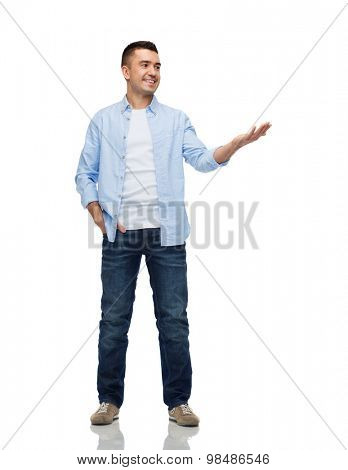 happiness, gesture and people concept - smiling man showing something imaginary on empty palm