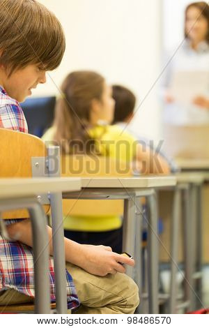 education, elementary school, learning, technology and people concept - close up of school boy with smartphone on lesson at classroom