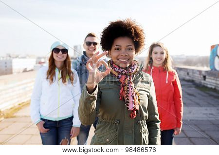 people, friendship and international concept - happy african american young woman or teenage girl in front of her friends showing ok sign on city street