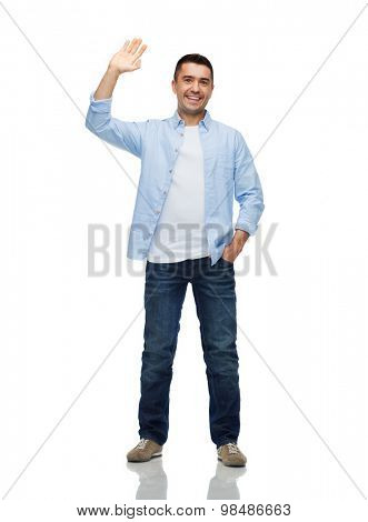 happiness and people concept - smiling man in shirt and jeans waving hand