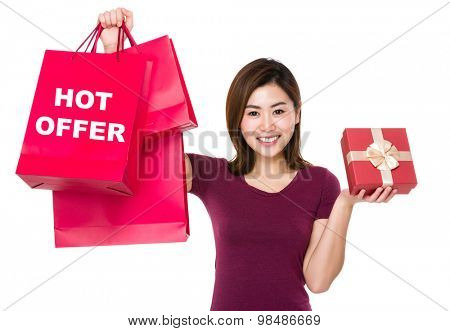 Woman hold with shopping bag and giftbox showing hot offer