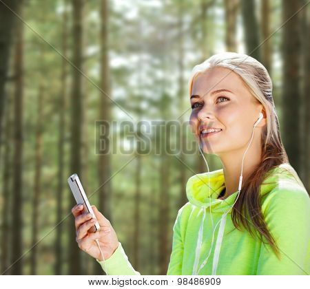 people, sport, fitness and technology concept - happy woman with smartphone and earphones listening to music over woods background