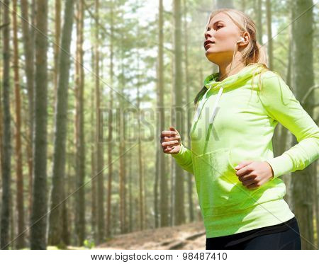 people, sport, fitness and slimming concept - happy woman running or jogging over woods background