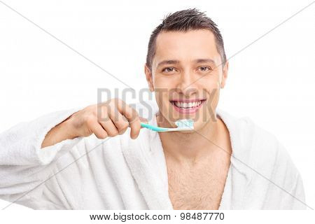 Young man in a white bathrobe holding a toothbrush and looking at the camera isolated on white background