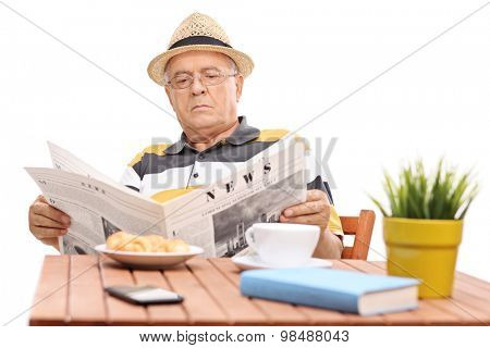 Mature man reading a newspaper seated at a coffee table with few croissants on it.The newspaper is custom made, text is Latin and the pictures are my copyright. Additionally property release uploaded.
