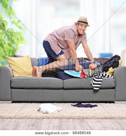 Young guy packing clothes into a briefcase on a gray sofa at home shot with tilt and shift lens