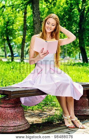 Pretty young woman reading a book sitting on the bench on a sunny summer day.