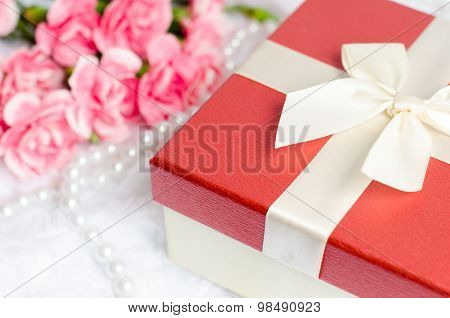 Close Up Of Gift Box With Pearl Necklace And Pink Carnation Flower On White Fur