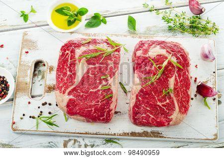 Raw Rib Eye Steaks  On A White Cutting Board.