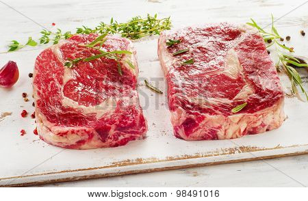 Raw Rib Eye Steaks  On A Cutting Board.