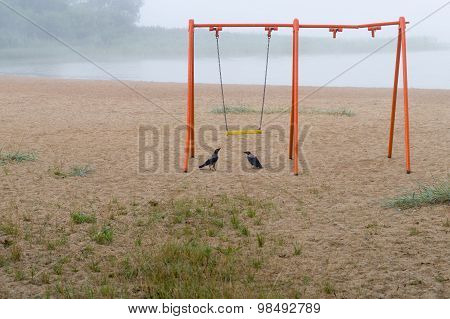Old Orange Swing And Two Crows On The Beach, Foggy Lake On Background
