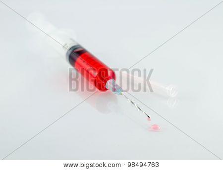 Medical Syringe With Drop On White Background