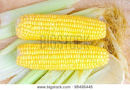 Sweetcorns And Cob On Wooden Table