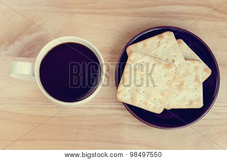 Cup Of Coffee On Wooden Table With Cracker In Plate : Top View