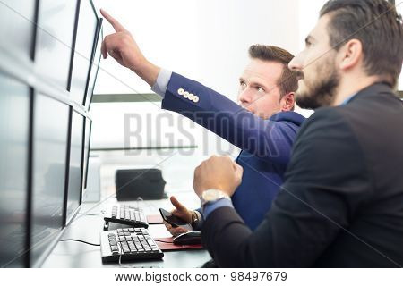 Stock traders looking at computer screens.