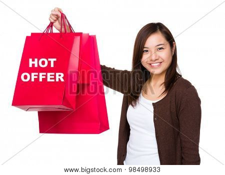 Asian woman holding with shopping bag and showing hot offer