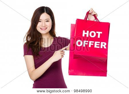 Asian woman with finger point to shopping bag and showing hot offer