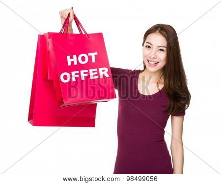 Asian woman hold with shopping bag and showing hot offer