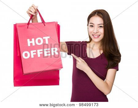 Woman finger point to shopping bag and showing hot offer