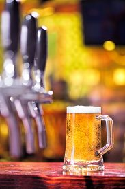stock photo of tapping  - Shallow depth of field shot of beer tap machine with blurred golden background - JPG