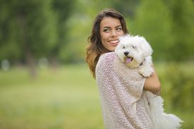 picture of maltese  - Young woman with a maltese dog outside - JPG