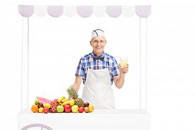 picture of jerks  - Senior soda jerk holding a glass of lemonade and standing behind a stall with a bunch of fruits on it isolated on white background - JPG