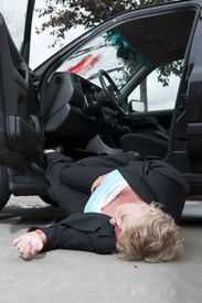 image of accident victim  - An injured driver with a severe head wound lies unconsciously on the ground fallen from her vehicle after an accident - JPG