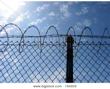 Fence Post On Chain Link Fence With Barb And Razor Wire