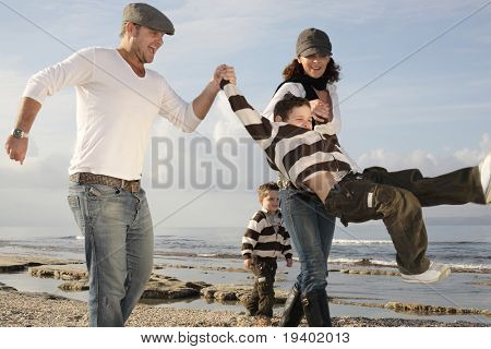 happy family of four playing on the beach