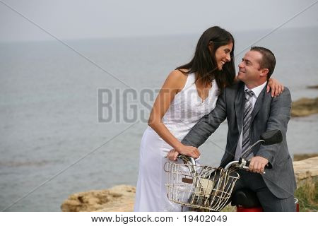 Just Married - smiling bride and groom with aged motorcycle