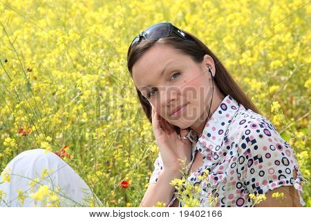 pretty young woman wearing earphones listening to music on a meadow