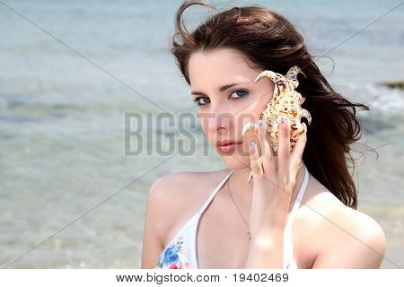 beautiful teen girl in swimwear holding up a seashell