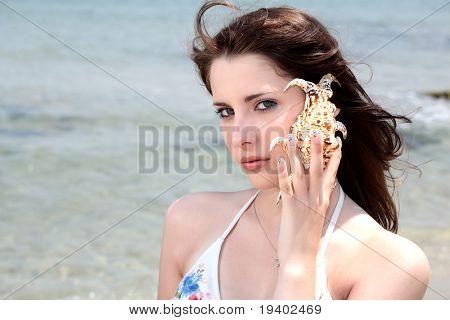 beautiful teen girl in swimwear holding up a seashell