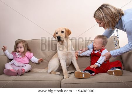 A young boy and girl with Downs Syndrome at a dog therapy session with mom