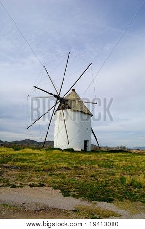 Typical spanish windmill in a meadow, rural landscape with country road