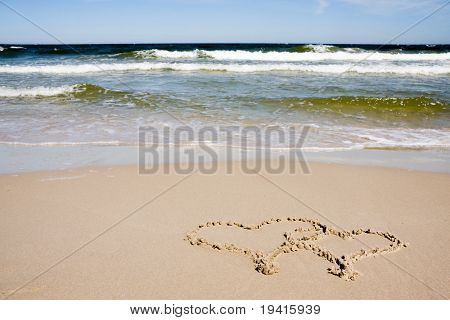 Two hearts drawn on a sandy beach in sunny day