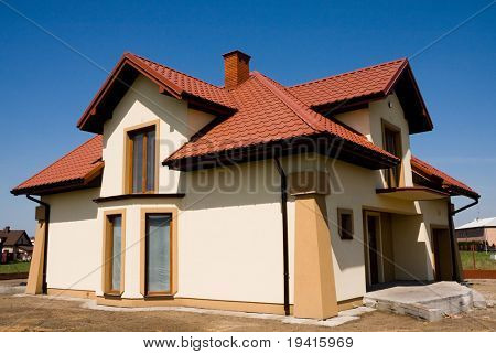 Incomplete single family small yellow house against blue sky
