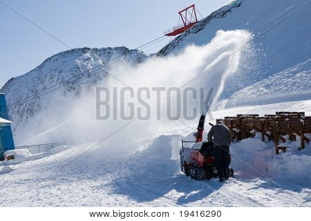 Worker removing snow with snowblower
