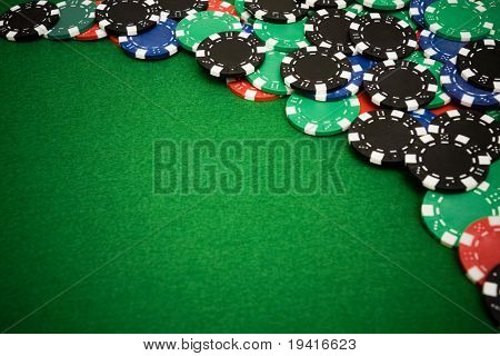 Colorful gambling chips on green felt background with copy space