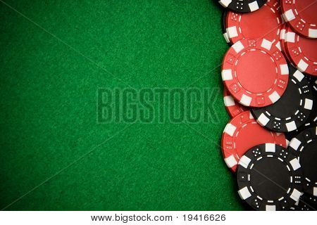 Black and red gambling chips on green felt background with copy space