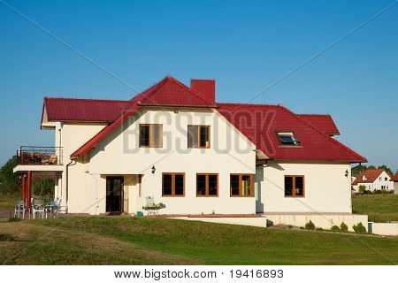 Single family yellow house with red roof over blue sky