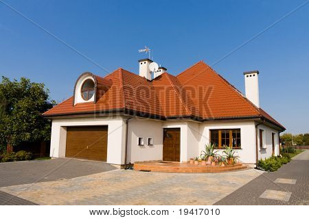 Single family white house with brown roof against blue sky