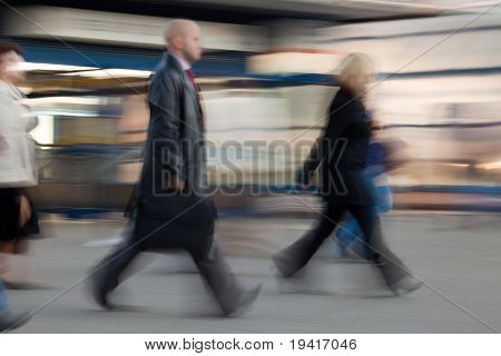 Businessman  with suitcase rushing to work at the morning in intentional motion blur.
