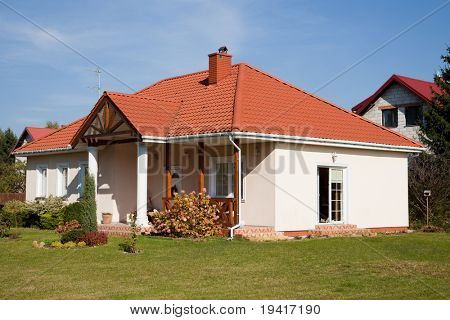 Single family small house in bright color against blue sky